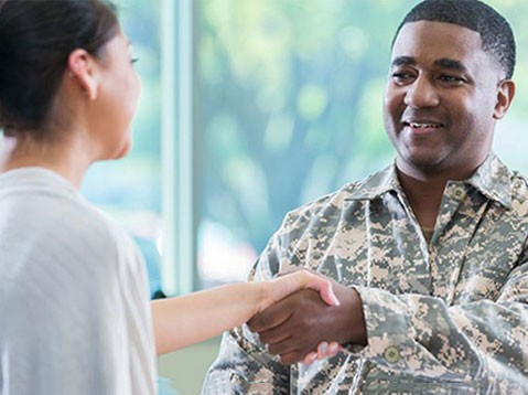 Man in military attire shakes a recruiter's hand at a job fair for military students, veterans and their spouses.