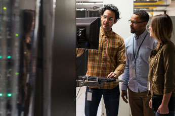 Three diverse technicians using a comuter in a server room.