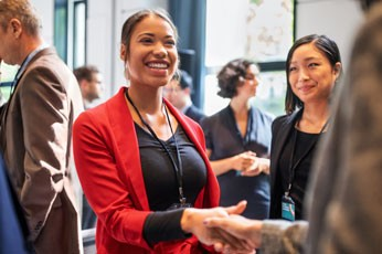 A businesswoman shaking hands at a networking event.