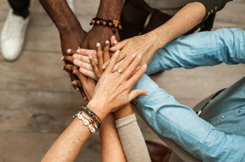 Five diverse team members stacking their hands to represent business team unity.