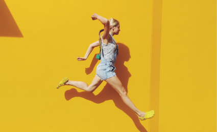 Young girl in denim overalls jumping in the air in front of a yellow wall