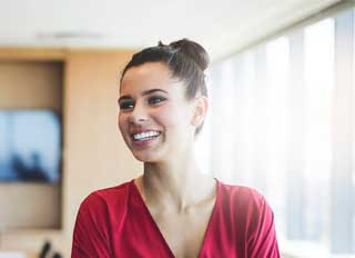 Young female with her hair in a bun smiles while working on interview coaching.