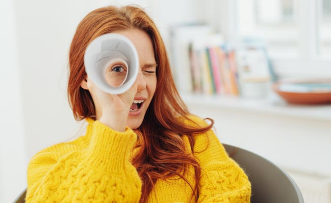 Happy red-headed woman wearing a yellow sweater looking through a paper telescope