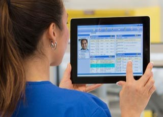Healthcare administration professional looking at a patient's electronic medical record on a tablet